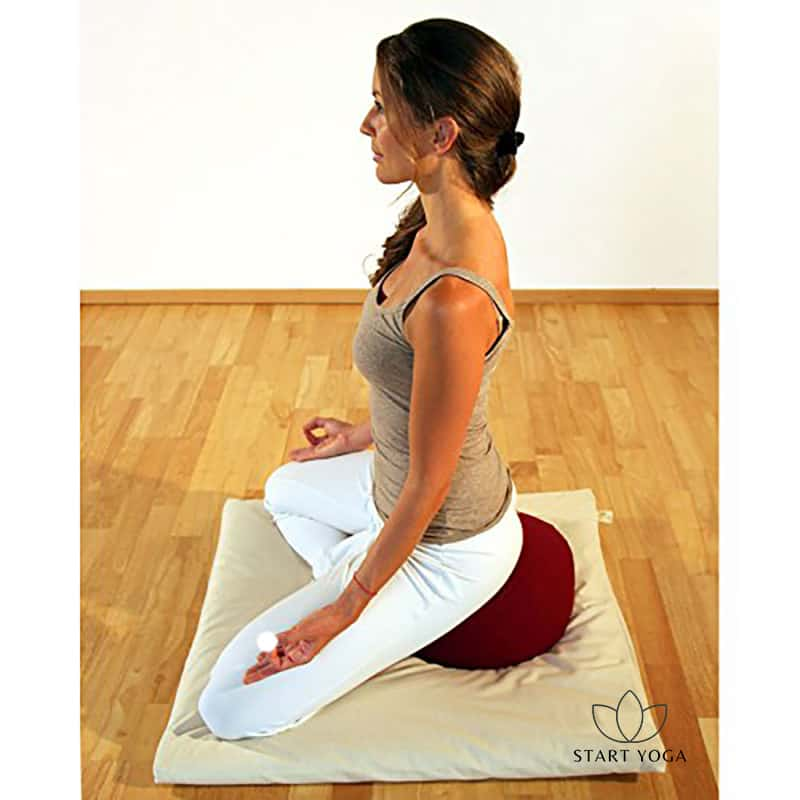 femme assise sur un coussin de yoga demi-lune et faisant de la méditation