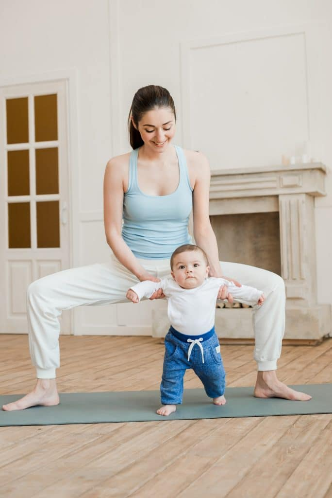 Mother with her child standing in yoga position on yoga mat at home