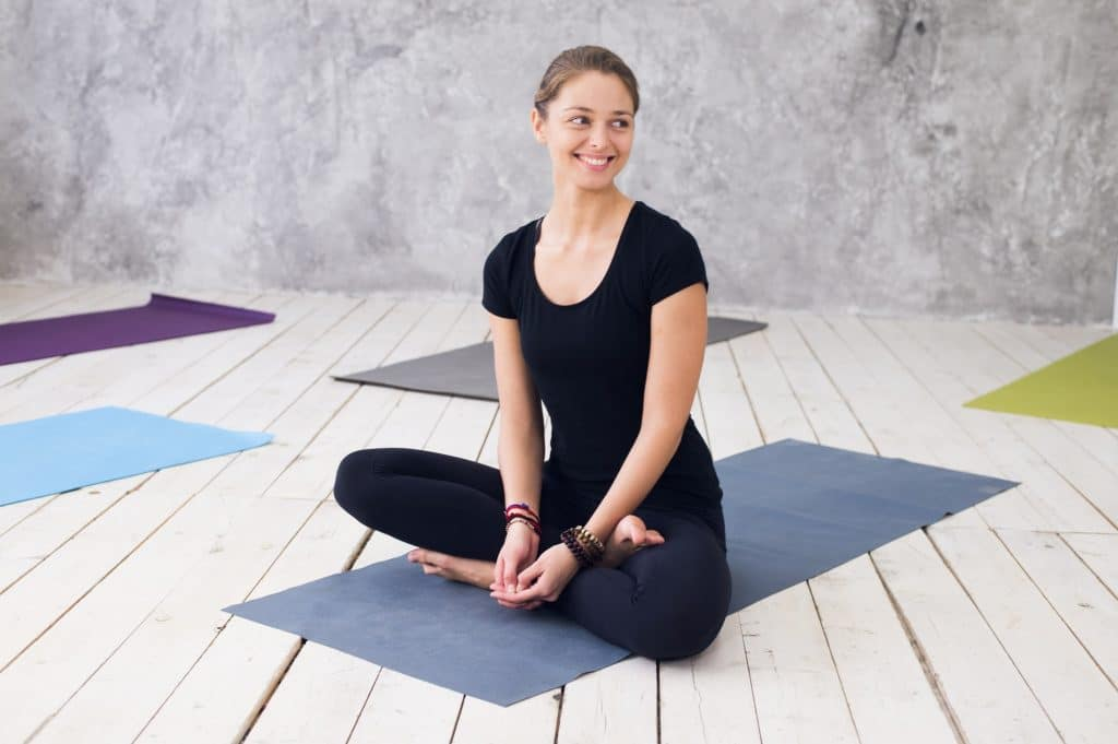 Young attractive woman practicing yoga, sitting in Ardha Padmasana exercise, Half Lotus pose