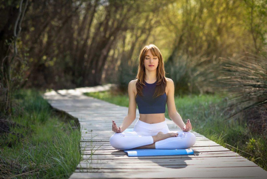 Jeune femme faisant du yoga dans la nature